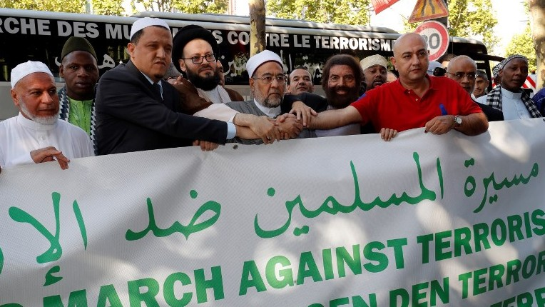 The Imam of Drancy, Hassen Chalghoumi (3L), writer Marek Halter (5R) and others pose with others behind a banner as they prepare to take part in The Muslim March Against Terrorism in Paris on July 8, 2017. (AFP PHOTO / FRANCOIS GUILLOT)