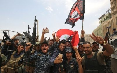 Members of the Iraqi federal police dance and wave their country's national flag in celebration in the Old City of Mosul on July 8, 2017, as their part of the battle has been declared accomplished, while other forces continue to fight Islamic State (IS) jihadists in the city. (AFP/Ahmad Al-Rubaye)