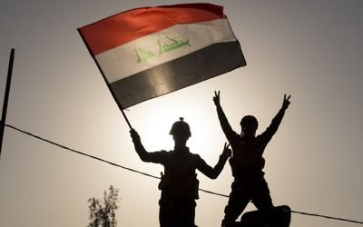 Iraq's federal police members wave an Iraqi flag as they celebrate in the Old City of Mosul on July 9, 2017. (AFP Photo/Fadel Senna)