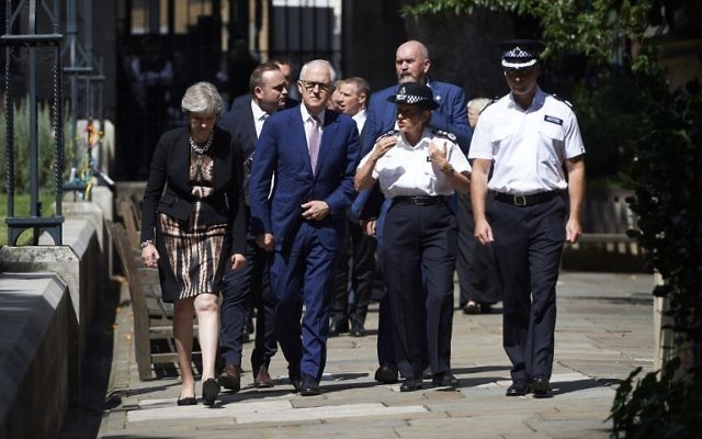 Britain's Prime Minister Theresa May, left, Australian Prime Minister, Malcolm Turnbull, center, and police officials walk outside Southwark cathedral during a visit to the Borough Market area of London in central London on July 10, 2017, the scene of a June 3 terror attack. (AFP/ POOL / Niklas HALLEN)
