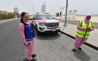 Filipino doctor Maria Lagbes (L) and a driver stand next to a pink ambulance of the Women Responders team in Dubai on July 13, 2017. (AFP PHOTO / GIUSEPPE CACACE)
