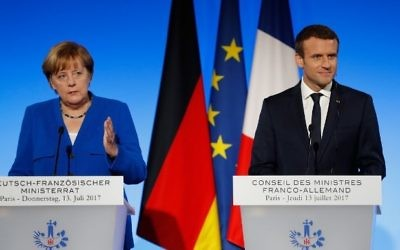 German Chancellor Angela Merkel (L) and French President Emmanuel Macron deliver a joint press conference at the Elysee Palace in Paris, on July 13, 2017. (AFP Photo/Patrick Kovarik)