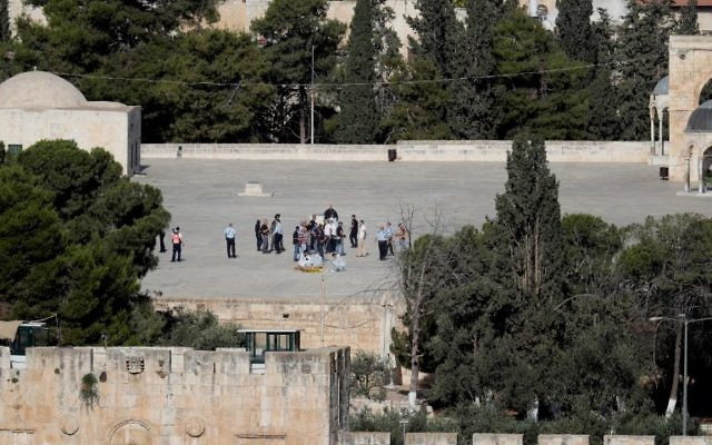 Police check the scene and surround a dead body (foreground) where Arab Israeli attackers shot and killed two Israeli policemen on the Temple Mount on July 14, 2017. (AFP Photo/Thomas Coex)