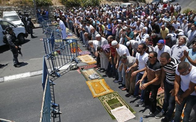 Muslim worshippers pray on a street outside the Lions Gate near Jerusalem's Temple Mount on July 14, 2017, after three Arab Israelis assailants killed two Israeli police officers there (AFP PHOTO / AHMAD GHARABLI)