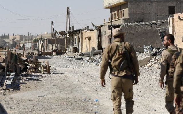 Members of the Syrian Democratic Forces (SDF), an alliance of Kurdish and Arab fighters, walk along a damaged street in eastern Raqqa, Syria, July 14, 2017.  (AFP/Bulent Kilic)