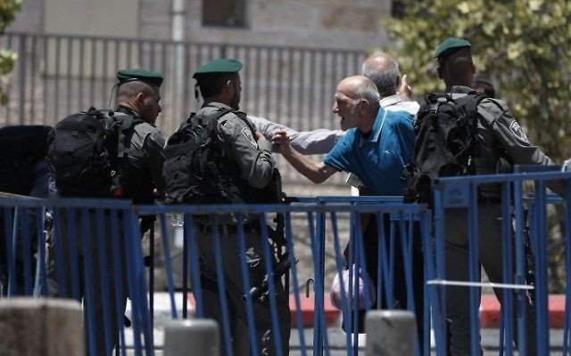 A Palestinian man speaks with an Israeli border police standing guard outside Damascus Gate, a main entrance to Jerusalem's Old City, on July 15, 2017 (AFP PHOTO / AHMAD GHARABLI)