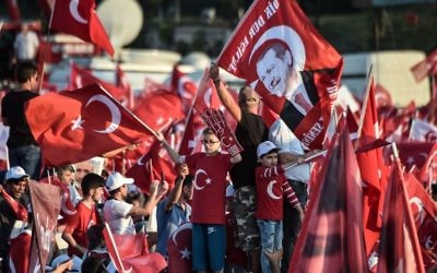 "People wave Turkish national flags as they stand near the ""July 15 Martyrs Bridge"" (Bosphorus Bridge) in Istanbul on July 15, 2017.(AFP PHOTO / OZAN KOSE)"