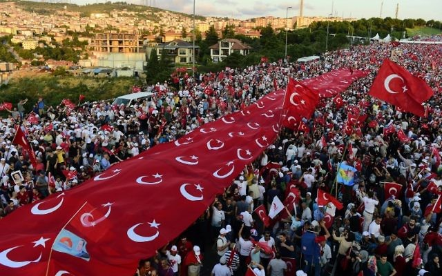 """People stand under a collection of Turkish national flags as they gather on the """"July 15 Martyrs Bridge"""" (Bosphorus Bridge) in Istanbul on July 15, 2017. (AFP PHOTO / YASIN AKGUL)"""