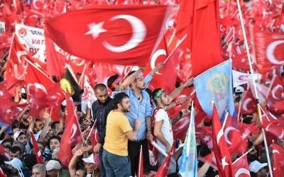 People wave Turkish national flags as Turkish President Recep Tayyip Erdogan addresses a speech on July 15, 2017 during the first anniversary of the failed coup in Istanbul.(AFP PHOTO / OZAN KOSE)