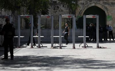 Israeli border policemen install metal detectors outside the Lion's Gate, a main entrance to the Temple Mount, in Jerusalem's Old City, on July 16, 2017, after security forces reopened the ultra-sensitive site, whose closure after a deadly attack earlier in the week sparked anger.  (AFP/ AHMAD GHARABLI)