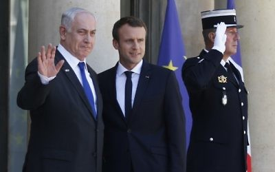 Prime Minister Benjamin Netanyahu (L) waves as he stands next to French President Emmanuel Macron (R) upon his arrival at the Elysee Palace, in Paris, on July 15, 2017 ahead of their meeting. (AFP PHOTO / GEOFFROY VAN DER HASSELT)
