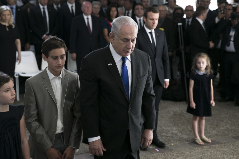 "Israeli Prime Minister Benjamin Netanyahu pays his respects after laying a wreath during a ceremony commemorating the 75th anniversary of the Vel d'Hiv roundup in Paris on July 16, 2017. French President Emmanuel Macron on July 16 marked 75 years since the roundup of some 13,000 Jews to be sent to Nazi death camps, calling France's responsibility a ""stark truth."" (AFP PHOTO / POOL / Kamil Zihnioglu)"