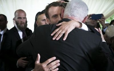 French President Emmanuel Macron embraces Israeli Prime Minister Benjamin Netanyahu during a ceremony commemorating the 75th anniversary of the Vel d'Hiv roundup in Paris on July 16, 2017.  (AFP PHOTO / POOL / Kamil Zihnioglu)
