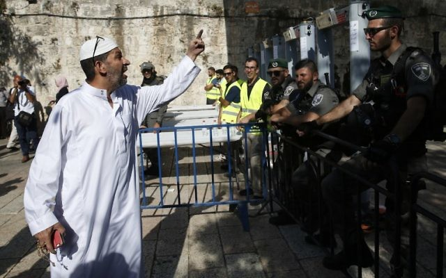 A Palestinian man argues with Israeli border policemen standing guard near new-installed metal detectors at a main entrance to the Temple Mount in Jerusalem's Old City, on July 16, 2017, after security forces reopened the ultra-sensitive site.  ( AFP PHOTO / AHMAD GHARABLI)