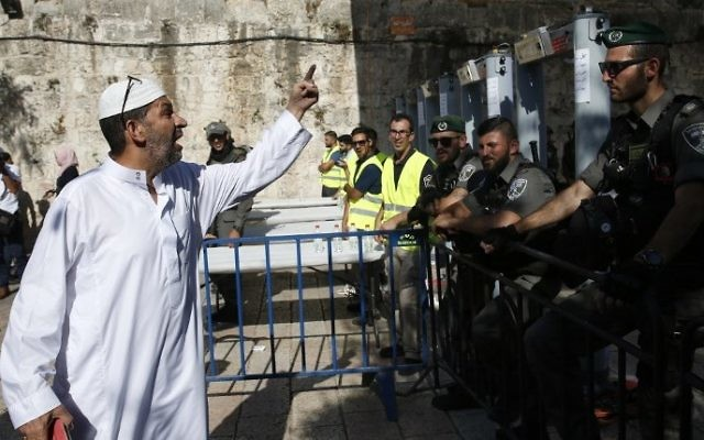A Palestinian man argues with Israeli border policemen standing guard near newly-installed metal detectors at a main entrance to the Al-Aqsa mosque compound in Jerusalem's Old City,  July 16, 2017, after security forces reopened the ultra-sensitive site. (AFP PHOTO / AHMAD GHARABLI)