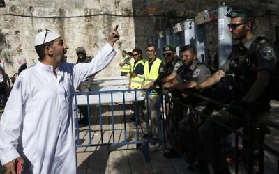 A Palestinian man argues with Israeli border policemen standing guard near newly installed metal detectors at a main entrance to the Temple Mount, on July 16, 2017. (AFP/Ahmad Gharabli)