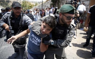 Illustrative: Israeli border guards detain a Palestinian youth during a demonstration outside the Lions Gate in Jerusalem's Old City on July 17, 2017. (AFP/ AHMAD GHARABLI)