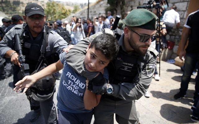 Israeli border guards detain a Palestinian youth during a demonstration outside the Lions Gate in Jerusalem's Old City on July 17, 2017. (AFP/AHMAD GHARABLI)