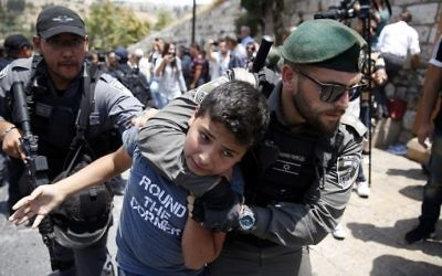 Israeli border guards detain a young protester during a demonstration outside the Lions Gate in Jerusalem's Old City on July 17, 2017. (AFP Photo/Ahmad Gharabli)