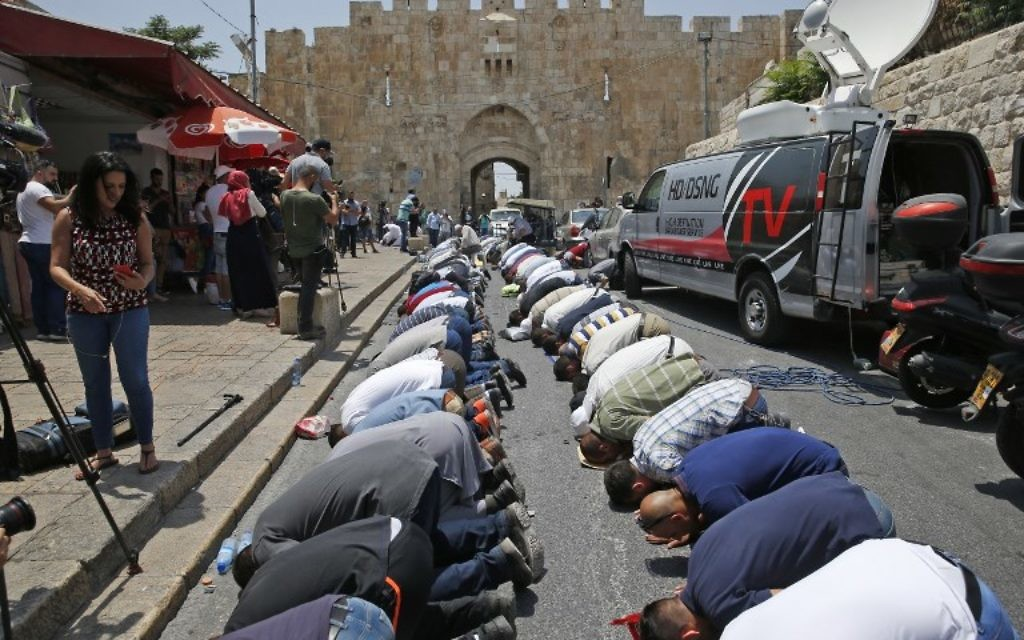 Muslim worshipers who refuse to enter the Temple Mount due to newly implemented security measures by Israeli authorities pray outside the Lions Gate in Jerusalem's Old City on July 17, 2017. (AFP/AHMAD GHARABLI)