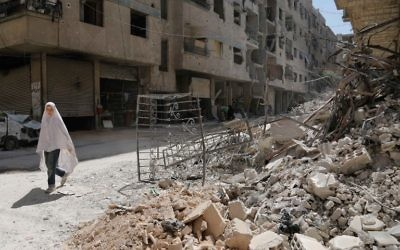 A girl walks past the rubble of a destroyed building down a street in the rebel-held Syrian town of Ayn Tarma, in the Ghouta area east of the capital Damascus, July 19, 2017. (AFP/ABDULMONAM EASSA)