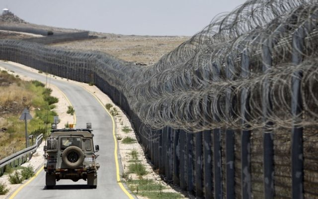 An IDF vehicle drives along the road parallel to the border fence separating the Israeli and Syrian regions of the Golan Heights, July 19, 2017. (AFP/MENAHEM KAHANA)
