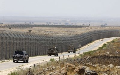 IDF vehicles driving along the road parallel to the border fence separating the Israeli and Syrian regions of the Golan Heights, July 19, 2017. (AFP/MENAHEM KAHANA)