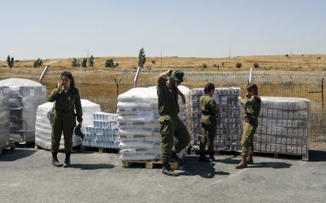 IDF soldiers stand next to food supplies being prepared as humanitarian aid for Syrian's impacted by the civil war in their country, July 19, 2017. (AFP/MENAHEM KAHANA)