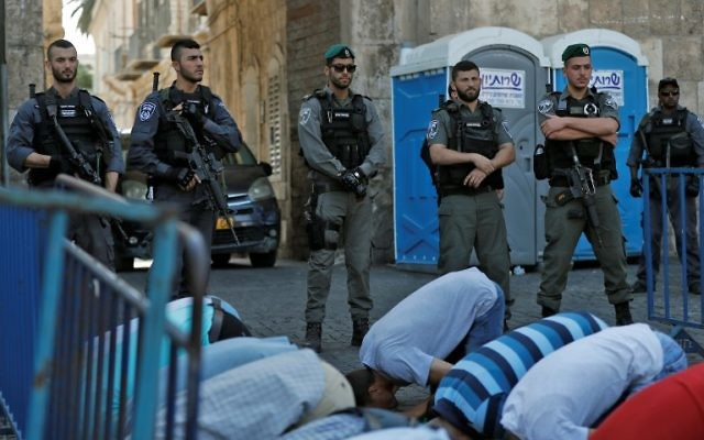 Israeli security forces stand guard in front of Palestinian Muslim worshipers praying outside Lions Gate, a main entrance to the Temple Mount compound in Jerusalem's Old City, on July 19, 2017(AFP PHOTO / Ahmad GHARABLI)