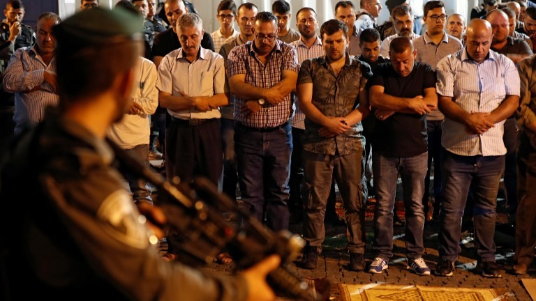 Israeli security forces stand guard in front of Muslim worshipers praying outside Lions Gate in Jerusalem's Old City, on July 19, 2017 AFP/ Ahmad GHARABLI)