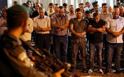 Israeli security forces stand guard in front of Palestinian Muslim worshipers praying outside Lions Gate, a main entrance to the Al-Aqsa Mosque compound in Jerusalem's Old City, on July 19, 2017, as the latter protest against new Israeli security measures implemented at the holy site (AFP PHOTO / Ahmad GHARABLI