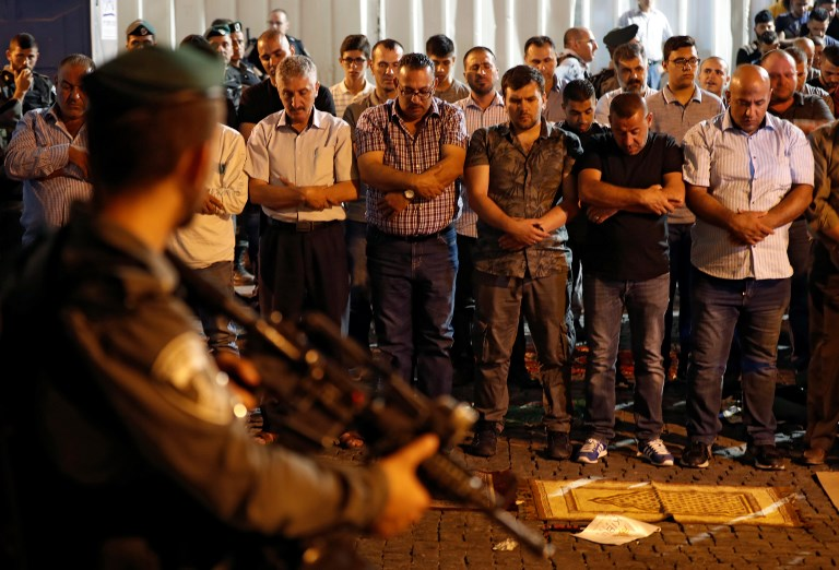Israeli security forces stand guard in front of Palestinian Muslim worshippers praying outside Lions Gate, a main entrance to Temple Mount compound in Jerusalem's Old City, on July 19, 2017, (AFP PHOTO / Ahmad GHARABLI)