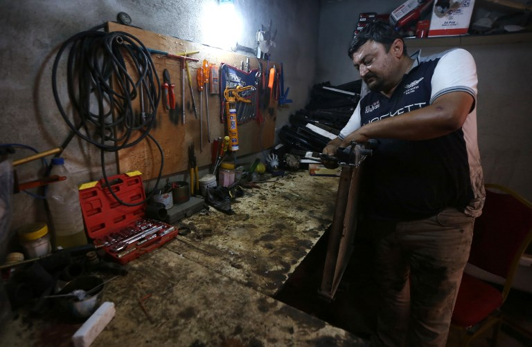 Haitham Behnam, a 34-year-old Iraqi Christian man who fled the violence in Mosul after Islamic State (IS) group militants seized control of the northern Iraqi city, works at his auto repair workshop in Arbil, the capital of the autonomous Kurdish region of northern Iraq, on July 20, 2017. (AFP PHOTO / SAFIN HAMED)