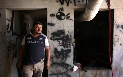 Haitham Behnam, a 34-year-old Iraqi Christian man who fled the violence in Mosul after Islamic State (IS) group militants seized control of the northern Iraqi city, stands at his auto repair workshop where he works as a mechanic in Arbil, the capital of the autonomous Kurdish region of northern Iraq, on July 20, 2017. (AFP PHOTO / SAFIN HAMED)