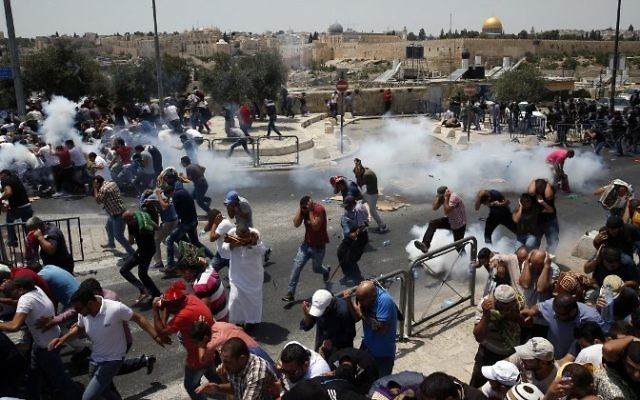 Palestinian worshipers run for cover from teargas, fired by Israeli security forces, following prayers outside Jerusalem's Old City in front of the Al-Aqsa mosque compound on July 21, 2017. (AFP/Ahmad Gharabli)