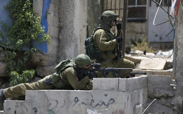 Israeli security forces hold a position during clashes between demonstrators and Israeli security forces at the Qalandiya checkpoint, between Ramallah and Jerusalem, in the West Bank, on July 21, 2017 (AFP PHOTO / ABBAS MOMANI)
