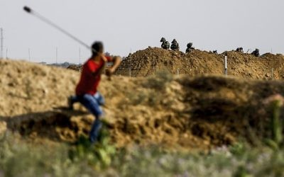 A Palestinian protester uses a sling to hurl a stone towards Israeli troops during clashes near the Gaza border fence east of Jabalia refugee camp on July 21, 2017. (AFP/Mohammed Abed)
