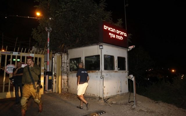An Israeli soldier stands guard at the gated entrance of the Halamish settlement, on July 22, 2017, a day after a Palestinian terrorist killed three Israelis there. (AFP PHOTO / GALI TIBBON)
