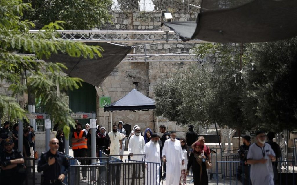 Muslim tourists walking past Israeli security measures as they exit the Temple Mount compound in the Old City of Jerusalem on July 23, 2017. (AFP PHOTO / Ahmad Gharabli)