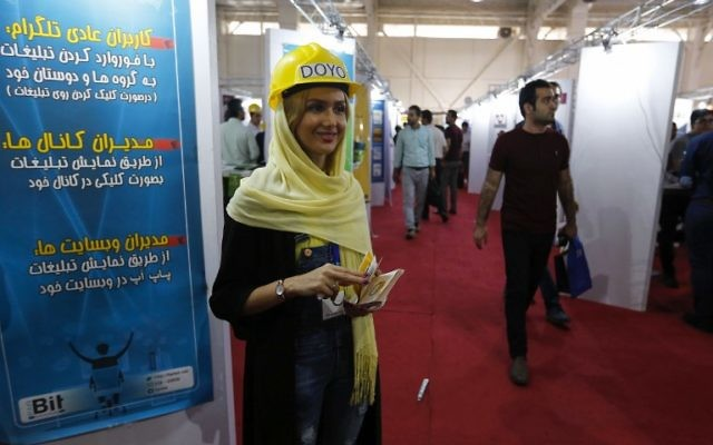 A hostess welcomes visitors during the Elecomp tech fair in the Iranian capital Tehran, July 23, 2017. (AFP/ATTA KENARE)