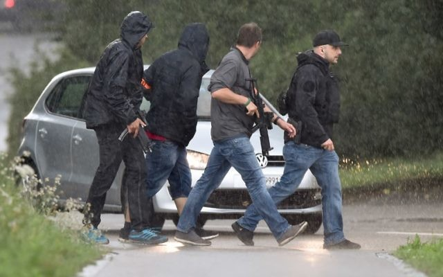 Police officers walk under heavy rain during the hunt in Uhwiesen northern Switzerland, for a man armed with a chainsaw who injured at least five people in an attack in Schaffhausen, July 24, 2017. (AFP/MICHAEL BUHOLZER)