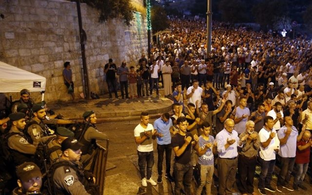 Israeli security forces stand by as Palestinian Muslim worshippers pray outside Lions Gate, a main access point to the Temple Mount compound in Jerusalem's Old City, July 24, 2017. (AFP/Ahmad GHARABLI)