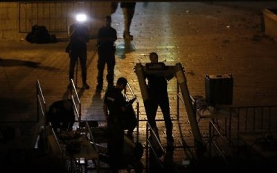 Israeli security forces take down metal detectors outside the Old City of Jerusalem's Lions Gate on July 24, 2017. (AFP Photo/Ahmad Gharabli)