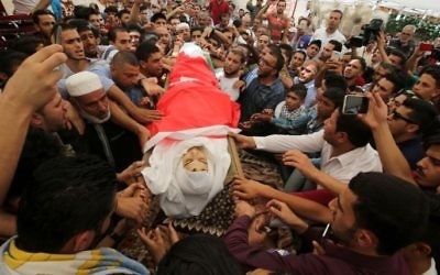 Mourners carry the body of 17-year-old Mohammed Jawawdeh, who was killed on the weekend when he attacked a security guard at the Israeli embassy compound in the Jordanian capital with a screwdriver, during his funeral in Amman on July 25, 2017. (Khalil Mazraawi/AFP)