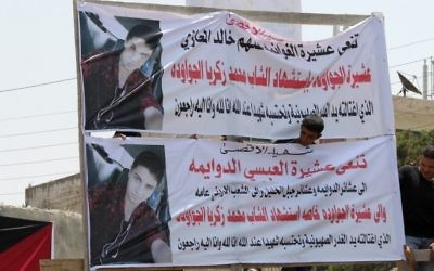 Mourners erect banners bearing the portrait of 17-year-old Mohammed Jawawdeh, who was killed on the weekend when he attacked a security guard at the Israeli embassy compound in the Jordanian capital with a screwdriver, during his funeral in Amman on July 25, 2017. (Khalil Mazraawi/AFP)
