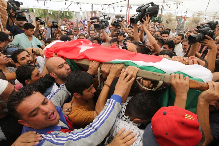 Mourners carry the body of 17-year-old Mohammed Jawawdeh, during his funeral on July 25, 2017, in Amman. (AFP PHOTO / KHALIL MAZRAAWI)