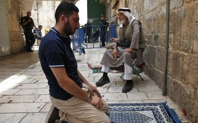 A Palestinian Muslim prays in the old city of Jerusalem on July 26, 2017, as a tense standoff between Israel and Muslim worshipers at the Temple Mount compound. (AFP PHOTO / AHMAD GHARABLI)