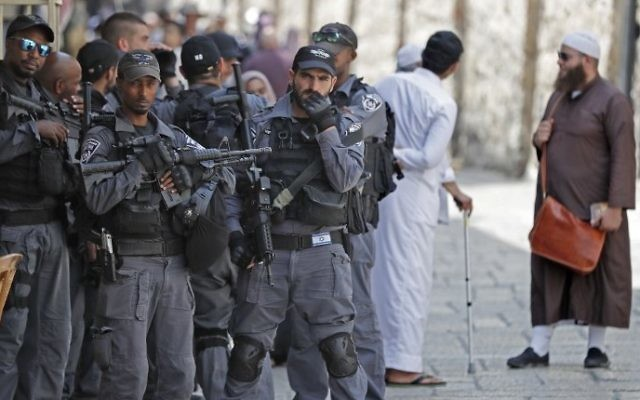 Israeli security forces stand by on guard as Palestinian Muslim worshipers gather to pray in the Old City of Jerusalem on July 26, 2017. AFP / AHMAD GHARABLI)