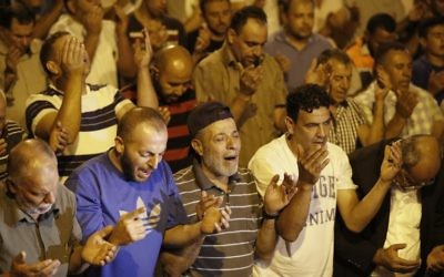 Palestinian Muslim worshipers pray outside Lions Gate, which leads to the Temple Mount compound in Jerusalem's Old City, on July 26, 2017 (AFP PHOTO / Ahmad GHARABLI)