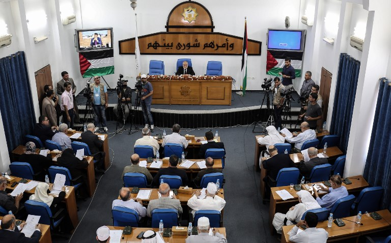 Hamas' MP and head of the parliament in Gaza City Ahmad Bahar (R) chairs a Palestinian legislative Council meeting in Gaza City as exiled former senior Fatah member Mohammed Dahlan attends it through video conference from the United Arab Emirates on July 27, 2017. (AFP PHOTO / SAID KHATIB)
